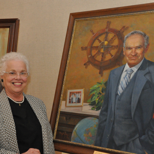 Molly Hudson, wife of the third director of the Memorial Union: Bruce Hudson, stands beside the new portrait of her late husband after it was donated